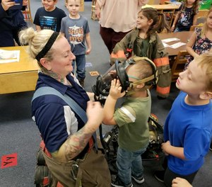 West Virginia firefighter Wendi Wentzell-Cuc shows a child her face mask during Fire Prevention Week. She and the department signed LION's