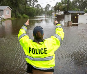 A City of Tybee police officer checks the well being of a resident fleeing her flooded home on Tybee Island, Ga.