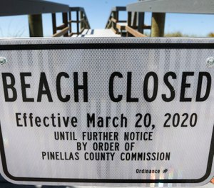 Pinellas County posted beach closure signs in March. On Thursday, the Pinellas County Commission will consider opening parts of the beaches for exercise, despite law enforcement's resistance. (Photo/TNS)