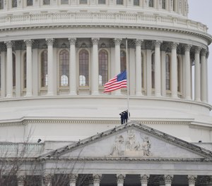 A flag is lowered to half-staff at the U.S. Capitol in honor of Officer Brian Sicknick, who died from injuries he sustained at the Capitol on Jan. 6 during a riot.