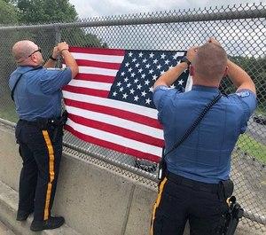 Robbinsville Township police officers hang an American flag on an overpass that runs through their Township. (Photo/Robbinsville Police Department via Facebook)