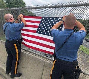 Robbinsville Township police officers hang an American flag on an overpass that runs through their Township.