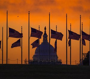 Flags fly at half-staff around the Washington Monument at daybreak in Washington with the US Capitol in the background Monday, June 13, 2016.