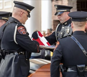 Lakeland Police Honor Guard Officer Suttle prepares to hand the flag to Lakeland Police Chief Ruben Garcia during the Police Honors ceremony for Officer Paul Dunn. (Photo/TNS)