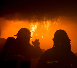 A firefighter with the Gowen Field Fire Department instructs a fellow firefighter on how to recognize the signs of flashover during a training in a specialized mobile burn trailer. (Photo/U.S. Air National Guard, Ryan White)