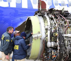 National Transportation Safety Board investigators examine damage to the engine of the Southwest Airlines plane that made an emergency landing at Philadelphia International Airport in Philadelphia on Tuesday. (Photo/AP)