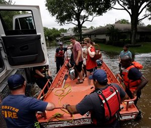 Members of the Houston and Webster fire departments help residents evacuate through the floodwaters surrounding their homes.