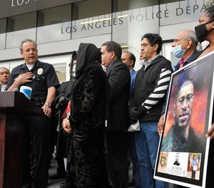 In this June 5, 2020, file photo, Los Angeles police chief Michel Moore, left, speaks as someone holds up a portrait of George Floyd during a vigil with members of professional associations and the interfaith community at Los Angeles Police Department headquarters in Los Angeles. (AP Photo/Mark J. Terrill, File)