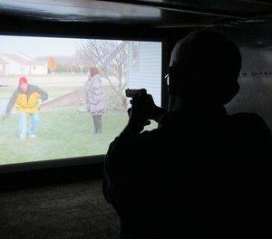 Mark Tulloch, of Kettering, Ohio, takes aim in a firearms training simulator at the Clark County Fair on Wednesday, July 26, 2017, in Springfield, Ohio.