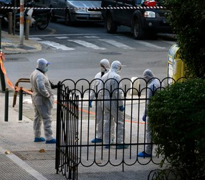 Greek forensic experts search at the scene after an explosion outside the Orthodox church of Agios Dionysios in the upscale Kolonaki area of Athens, Thursday, Dec. 27, 2018. Police in Greece say an officer has been injured in a small explosion outside a church in central Athens while responding to a call to investigate a suspicious package.
