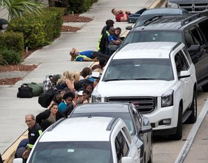 People take cover outside Fort Lauderdale–Hollywood International Airport, Friday, Jan. 6, 2017, in Fort Lauderdale, Fla., after a shooter opened fire inside a terminal of the airport, killing several people and wounding others before being taken into custody. (AP Photo/Wilfredo Lee)