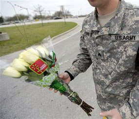 An unidentified soldier holds flowers dropped off at Fort Hood's main gate for shooting victims, Thursday, April 3, 2014, in Fort Hood, Texas.