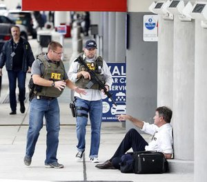 A law enforcement officers talk to a man at Fort Lauderdale–Hollywood International Airport, Friday, Jan. 6, 2017, in Fort Lauderdale, Fla.