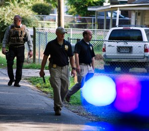 Georgia Bureau of Investigation agents and Hall County Sheriff's Office deputies work a crime scene along Highland Avenue, Monday, July 8, 2019, in Gainesville Ga. (Scott Rogers/The Times via AP)