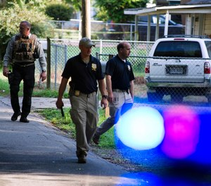 Georgia Bureau of Investigation agents and Hall County Sheriff's Office deputies work a crime scene along Highland Avenue, Monday, July 8, 2019, in Gainesville Ga.