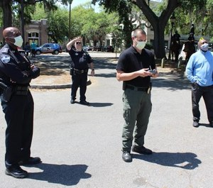 Police Chief Roy Minter (left) and other officers deploy a 'talking' drone to remind the public about social-distancing guidelines.