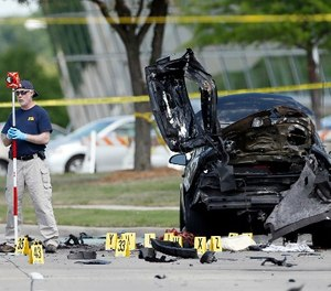 In this May 4, 2015 file photo, FBI crime scene investigators document evidence outside the Curtis Culwell Center in Garland, Texas.