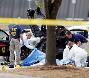 In this May 4, 2015 file photo, FBI crime scene investigators document the area around two deceased gunmen and their vehicle outside the Curtis Culwell Center in Garland, Texas.