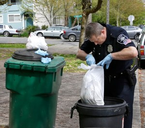 Seattle Police officer Aaron Stoltz searches garbage and recycling bins, Friday, April 15, 2016, after human remains were found in a nearby container in Seattle. (AP Photo/Ted S. Warren)