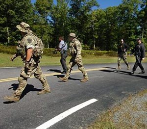 Members of the Pennsylvania State Police and law enforcement conservation officers with the Pennsylvania Game Commission walk from the state police barracks to a wooded area across the street on Route 402 to investigate near where two Pennsulvania State troopers were ambushed Friday, on Sunday, Sept. 14, 2014, in Blooming Grove Township, Pa.