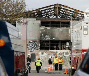 This Dec. 7, 2016 file photo members of the Alameda County Sheriff's Office stand outside the warehouse called the Ghost Ship the site of a fire, in Oakland, Calif.