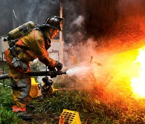 Army Pvt. 1st Class Lucas Ternell puts out a small debris fire in a yard in Salisbury, Md.