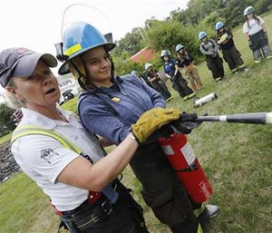 In this Monday, July 11, 2016 photo, Lt. Lyn Moraghan, left, instructs Tara Sivak in the use of a fire extinguisher during firefighting camp for girls at a fire station in Ashland, Mass. (AP Image)