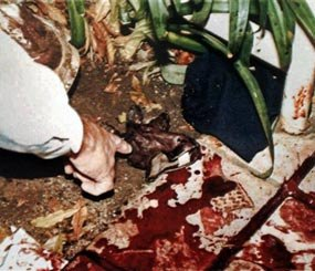 This June 13, 1994, LAPD evidence file photo shows Los Angeles Police Department's Mark Fuhrman pointing to a pieces of evidence near the body of Nicole Brown Simpson on the bloodstained walkway of her condominium. The O.J. Simpson trial has become a textbook example of what not to do at a crime scene for police and forensic workers. (AP Image)