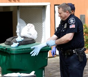 Seattle Police officer Aaron Stoltz puts on a glove as he prepares to search garbage and recycling bins, Friday, April 15, 2016, after human remains were found in a nearby container in Seattle.
