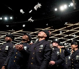 The newest members of the New York City police toss their gloves into the air during their graduation ceremony, Thursday, June 29, 2017, in New York.