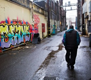 A person walks through an alley decorated with graffiti messages in downtown Aberdeen, Wash., Thursday, June 15, 2017.
