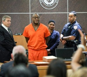 Lydell Grant, second from left, smiles in court after he was ordered to be released while authorities reinvestigate his case. (Photo/AP)
