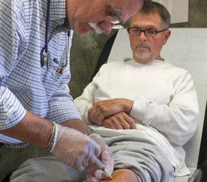 In this Sept. 12, 2012, file photo Dr. David Mathis gives a cortisone shot to the knee of inmate Edwin Bergman at the California Medical Facility in Vacaville, Calif.