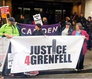 Protesters outside the Grenfell Tower public inquiry in central London where Sir Martin Moore-Bick is delivering his opening statement during its first preliminary hearing. (Jack Hardy/PA via AP)