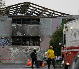 Fire officials walk past the remains of the Ghost Ship warehouse damaged from a deadly fire in Oakland, Calif.