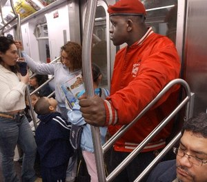 Guardian Angel Eric Jackson, right, looks around while patrolling a subway car in New York, Thursday, June 19, 2003.