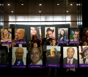 In this Dec. 7, 2015, file photo, San Bernardino County employees hold up photos of the San Bernardino shooting victims during a candlelight vigil in San Bernardino, Calif.