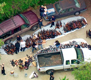 investigators from the U.S. Bureau of Alcohol, Tobacco, Firearms and Explosives and the police inspecting a large cache of weapons seized at a home in the affluent Holmby Hills area of Los Angeles Wednesday, May 8, 2019. (KCBS/KCAL-TV via AP)