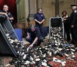 Guns are seen on display during a news conference regarding the