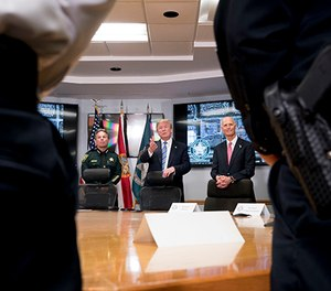 President Donald Trump, center, accompanied by Broward County Sheriff Scott Israel, left, and Florida Gov. Rick Scott, right, speaks as they meet with law enforcement officers at Broward County Sheriff's Office in Pompano Beach, Fla., Friday, Feb. 16, 2018, following Wednesday's shooting at Marjory Stoneman Douglas High School, in Parkland, Fla.