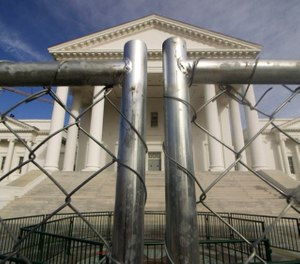 The Virginia state Capitol building is surrounded by fencing in preparation for Monday's rally. Gun-rights groups are asking a judge to block the Virginia governor's ban on firearms at a massive pro-gun rally scheduled for next week. (Photo/AP)