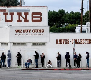 In this March 15, 2020, file photo, people wait in line to enter a gun store in Culver City, Calif. Los Angeles County Sheriff Alex Villanueva said that he is abandoning the effort to shut down firearms dealers.