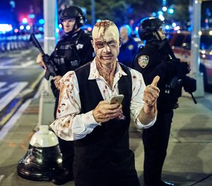 In this Oct. 31, 2017 file photo, a reveler gets his picture taken by a friend in front of heavily armed police during the Greenwich Village Halloween Parade in New York. The NYPD says thousands of uniformed and plainclothes officers will patrol the 2018 parade in Greenwich Village. They'll be joined by counterterrorism units, police dogs and helicopters.