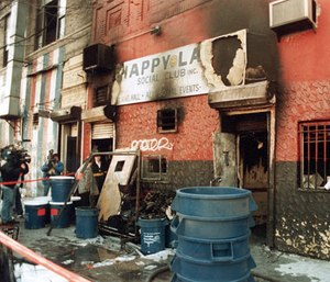 In this 1990 file photo, news crews report on an arson fire at the Happy Land social club in which 87 people perished, in the Bronx borough of New York. (AP Photo)