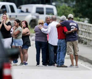 Family members react as a van is pulled out of the Greens Bayou with the bodies of six family members in Houston.
