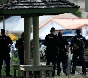 Honolulu police prepare to take defensive positions with their weapons after a shooting and domestic incident that left two Honolulu police officers dead. (Photo/AP)