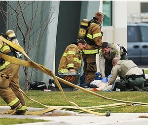 Rescue personnel from multiple agencies perform CPR on a patient at the site of a helicopter crash into a building. (AP Photo/Deseret News, Scott G Winterton)