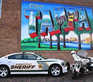Hillsborough County Sheriff's Office vehicles are posed beneath a mural of Tampa, the county seat.