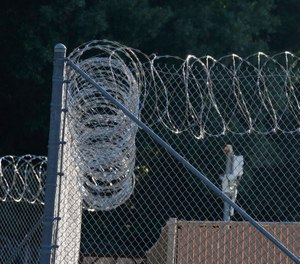 Early morning sun lights up the security fencing at the Hinds Detention Center in Raymond, Miss., Friday, June 12, 2015. ( AP Photo/Rogelio V. Solis)