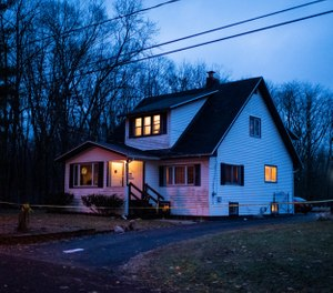 Police tape marks off the scene after authorities say an intruder shot and wounded several law enforcement officers at the home in Comstock Township, Mich. (Photo/AP)